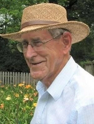 Photo of Stanley John Murdock wearing a straw hat, glasses, and a light blue shirt