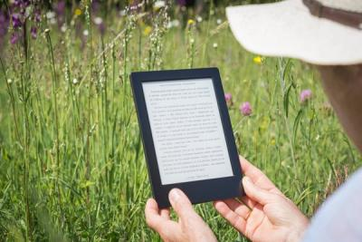 man reading ebook in field